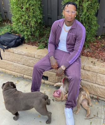 Moneybagg Yo Wearing A Purple Track Suit With A Rolex Watch And White Air Force 1s