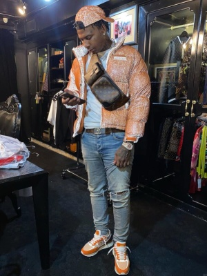 Moneybagg Yo Wearing A Supreme Orange Speckled Hat And Puffer Jacket With A Louis Vuitton Belt And Amiri Jeans