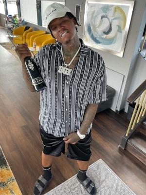Moneybagg Yo Wearing A White Balenciaga Hat With A Balenciaga Striped Shirt Black Pajama Short Black Logo Socks And Black Malloca Sandals