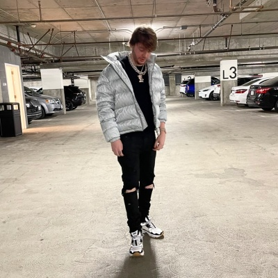 Murda Beats Wearing A Dior Silver Oblique Puffer Jacket With Dior Cd1 Sneakers And Black Ripped Jeans
