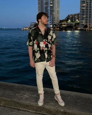 Murda Beatz Wearing A Black Floral Shirt With White Jeans And Dior Sneakers