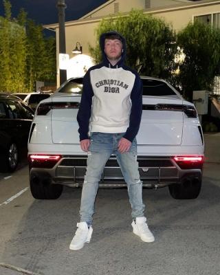 Murda Beatz Wearing A Dior X Kenny Scharf Varsity Logo Hoodie With Amiri Jeans And White Sneakers
