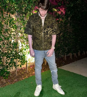 Murda Beatz Wearing A Givenchy Camo Zip Shirt With Amiri X Playboy Jeans And Nike X Comme Des Garcons Sneakers