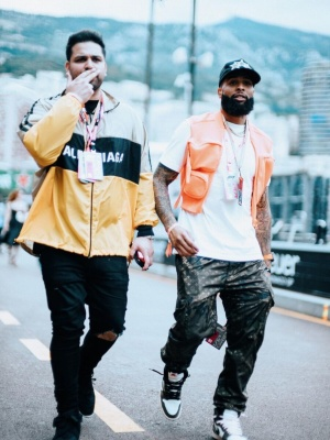Odell Backham Jr Wearing A Louis Vuitton Orange Vest White Tee And Lv X Supreme Camo Trackpants