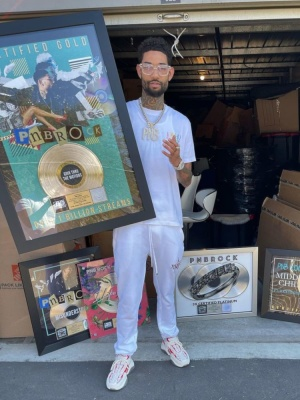 Pnb Rock Wearing An Amiri White And Rainbow Tee And Red Star Joggers With Red Skeleton Sneakers