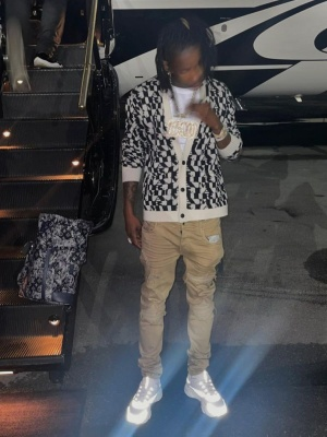 Polo G Wearing An Amiri Cardigan And Ribbed Khaki Pans With Dior Sneakers And A Louis Vuitton Backpack