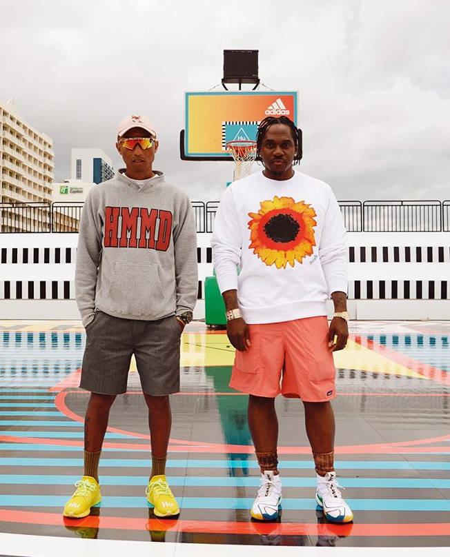 Pusha T With Pharrell Wearing A Noah Sunflower Sweatshirt Patagonia Short And Adidas X Pharrell White Sneakers