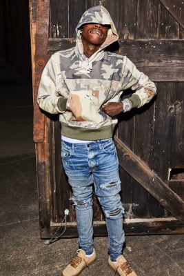 Quando Rondo Wearing An Amiri Camo Patchwork Hoodie And Camo Mx1 Patch Jeans