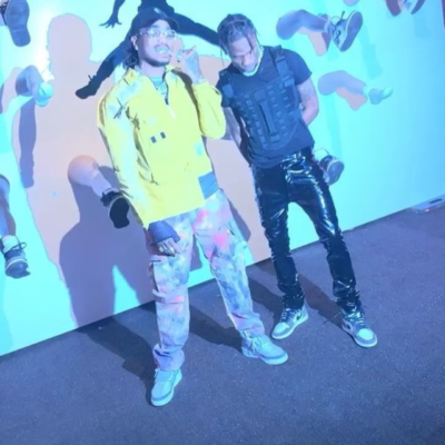 Quavo Wearing A Yellow A Cold Wall Polo Jacket And Paint Splatter Camo Pants With Travis Scott Wearing An Alyx Vest Black Shiny Pants And Cactus Jacket Sneakers
