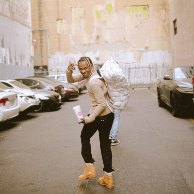 Rich The Kid Wearing A Beige Turtleneck With A White Backpack Black Jeans And Timerland Boots