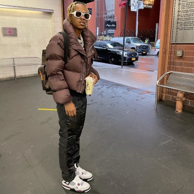 Rich The Kid Wearing A Brown Puffer With Black Pants And Jordan X Psg Sneakers