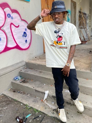 Rich The Kid Wearing A Gucci Bucket Hat With A Gucci X Disney T Shrit And Sneakers With A Patek Philippe Sneakers