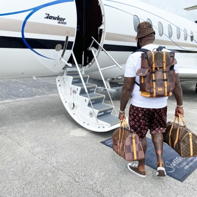 Rick Ross Boards His Jet With Full Louis Vuitton Bags