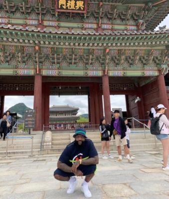 Rick Ross In Korea Wearing A Polo Ralph Lauren Bucket Hat And A Nautica Competition Print T Shirt