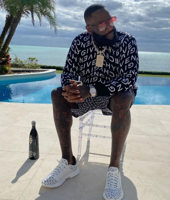 Rick Ross Wearing A Givenchy Refracted Sweater Refracted Swim Shorts And Refracted Sneakers