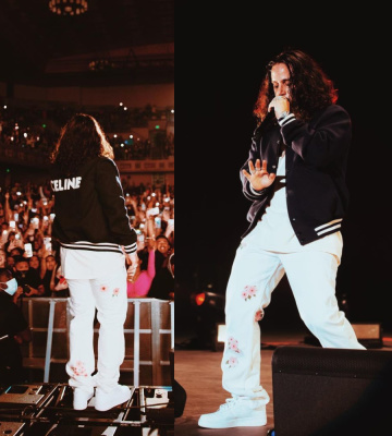 Russ Wearing A Celine Varsity Jacket With White Floral Jeans And Nike Air Force 1 Sneakers