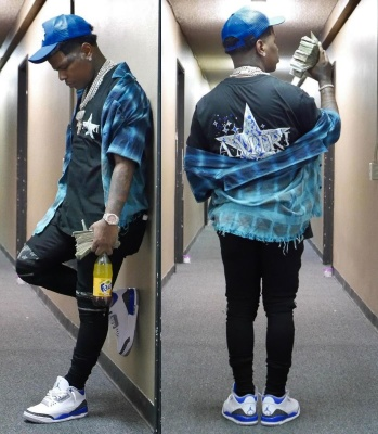 Rylo Rodriguez Wearing An Amiri Blue Hat Black Tee And Black Jeans With Jordan 3s