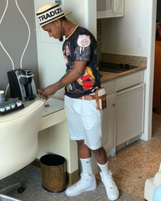 Slim Jxmmi Wearing A Straw Hat Black Dolce And Gabbana Shirt With A Gucci Cell Phone Case And White Pants