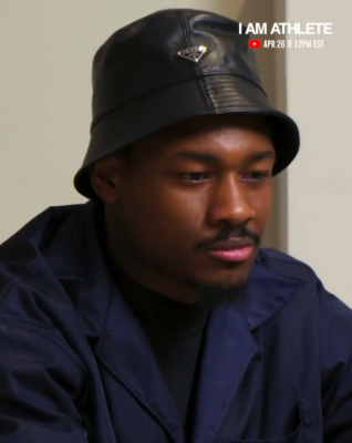 Stefon Diggs Wearing A Black Prada Leather Hat And Navy Nylon Pocket Shirt