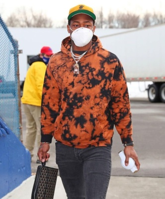 Stefon Diggs Wearing A Daniel Patrick Orarnge Black Tie Dye Hoodie With Grey Jeans And A Goyard Wash Bag