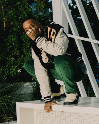 Tory Lanez Wearing An Amiri Jacket With Green Velour Pants And Bottega Veneta White And Clear Chelsea Boots