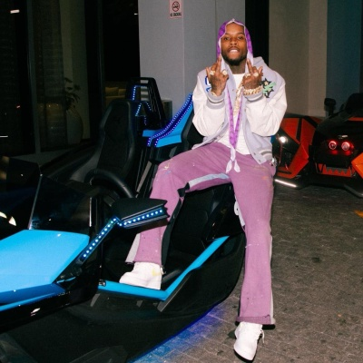 Tory Lanez Wearing An Off White Varsity Jacket With Purple Jeans And Nike White And Yellow Air Force 1s