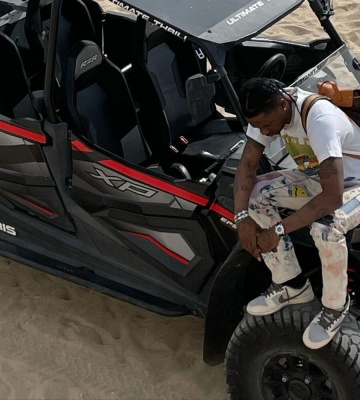 Travis Scott Wearing A Louis Vuitton Backpack With Kapital Jeans And Nike X Playstation Sneakers