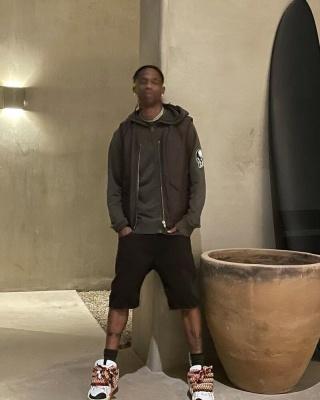 Travis Scott Wearing A Number Nine Vintage Hoodie With A Brown Vest And Sneakers