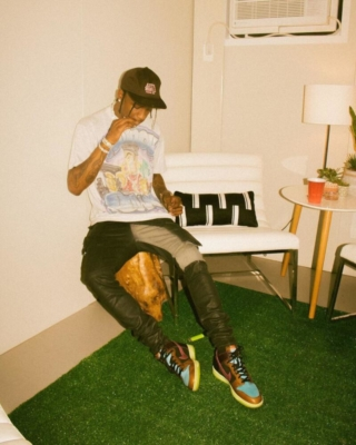 Travis Scott Wearing An Astroworld Hat Air Spray T Shirt Paneled Pants And Multicolor Nikes