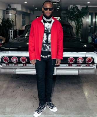 Ty Dolla Sign Wearing A Red Jacket Black Turtleneck Black Jeans And Jw Anderson Sneakers