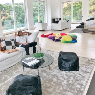 Tyga At Home Beside A Hermes Blanket And Pillows Wearing A White Tee With Off White Sweatpants