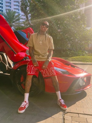 Tyga Wearing A 1017 Alxy 9sm Brown Logo Tee With Rhude Red Logo Short And Vans Low Red Checkerboard Sneakers