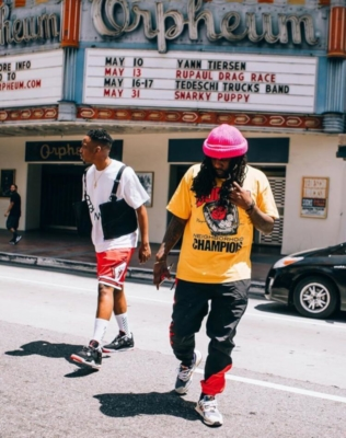 Wale In A Yellow Neighborhood Champions Shrit With Black Tracipants And Sneakers