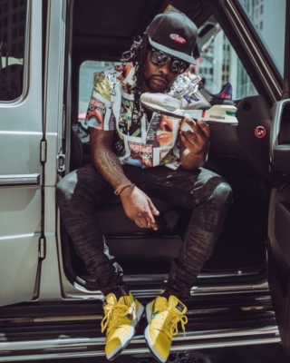 Wale Wearing A High Times Magazine Print Shirt With An Off White Hat And New Balance Sneakers