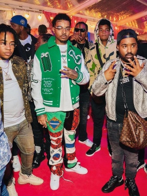 Wheezy Wearing A Louis Vuitton Green Varsity Jacket And T Shirt With Nike Air Force 1 Sneakers
