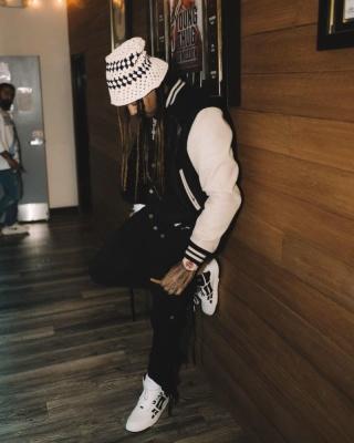 Wheezy Wearing An Amiri Crochet Hat White And Black Varsity Jacket Black Cargo Pants And White Bones Sneakers