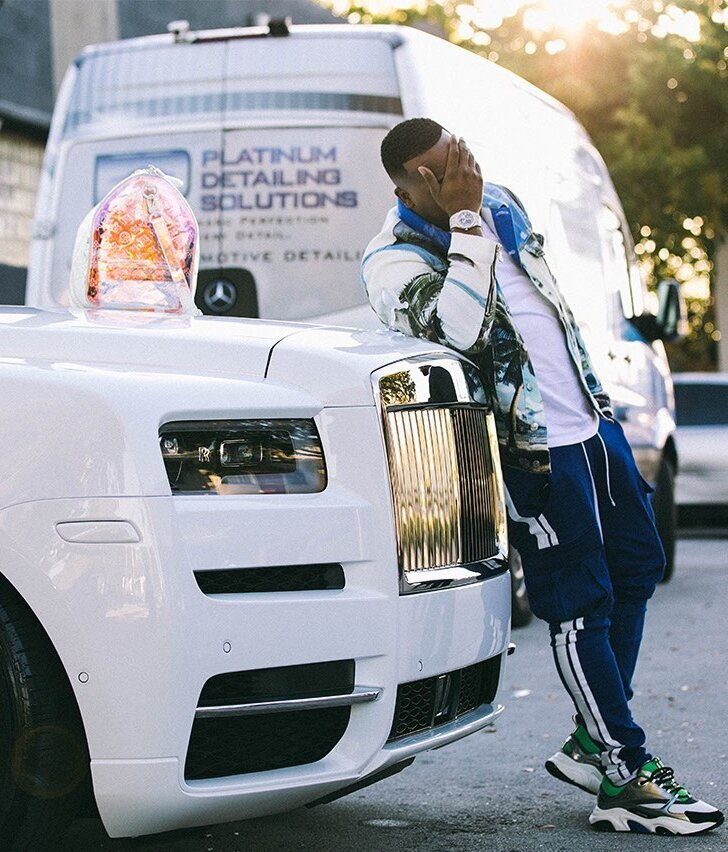 Yo Gotti Rests On His Rolls Roys In A Balmain Shirt Amiri Striped Blue Joggers With Dior Sneakers And A Lv Bag