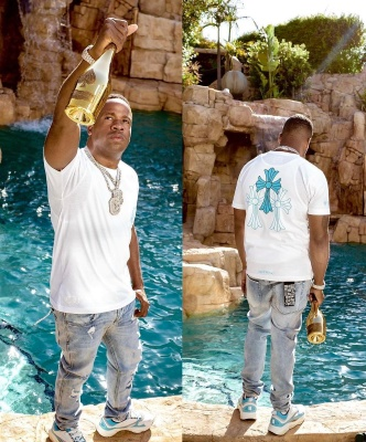 Yo Gotti Wearing A Chrome Hearts White And Light Blue Cross Tee With Ksubi Jeans And Dior Neon Blue B22 Sneakers