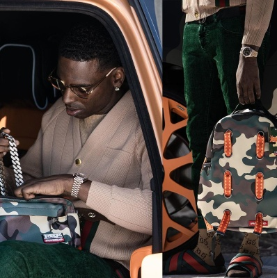 Young Dolph Wearing A Beige Gucci Cardigan With Gucci Sunglasses Green Jeans And Web Sandals