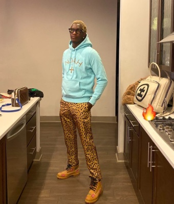 Young Thug Wearing A Noah Light Blue Hoodie With Cheetah Print Pants Timberland Boots And A White Bag